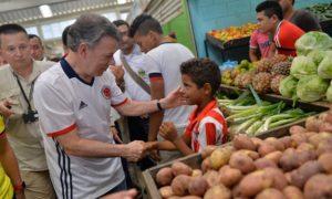 El Presidente Juan Manuel Santos saluda este viernes a un niño durante su recorrido por la plaza de mercado de Sahagún, Córdoba.