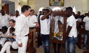 Durante la misa de este domingo en Bojayá, el Presidente de la República observa el Cristo mutilado que le entregó la comunidad de ese municipio del Chocó que sufrió la masacre ocurrida en 2002.
